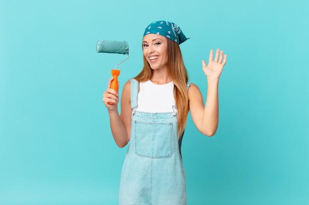 Ładna kobieta uśmiecha się radośnie, macha ręką, wita i wita cię malując nową ścianę domu
