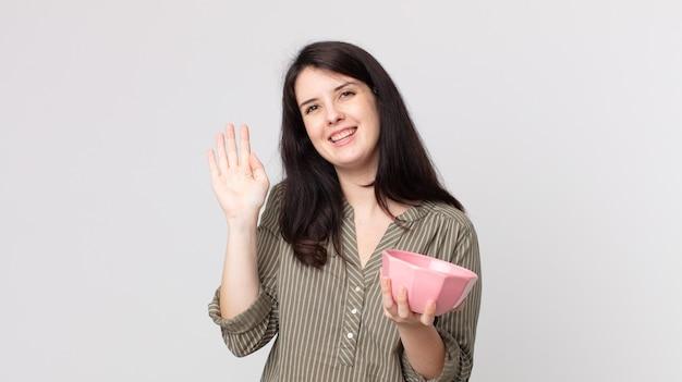 Ładna kobieta uśmiecha się radośnie, macha ręką, wita i wita cię, trzymając pustą miskę. asystent agenta z zestawem słuchawkowym