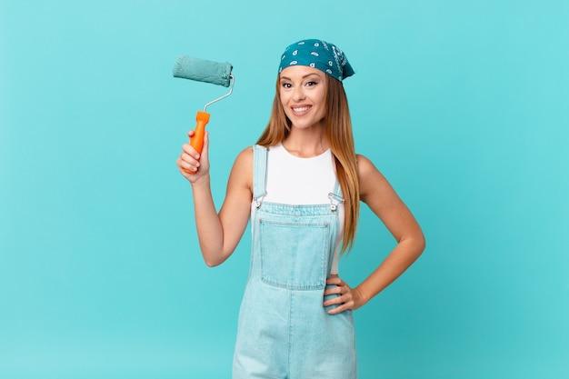 Ładna kobieta uśmiecha się radośnie z ręką na biodrze i pewnie maluje nową ścianę domu