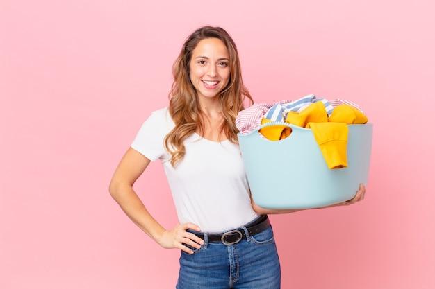 Ładna kobieta uśmiecha się szczęśliwie z ręką na biodrze i pewnie i pranie ubrań.