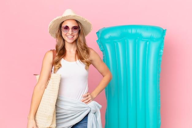 Ładna kobieta uśmiecha się szczęśliwie z ręką na biodrze i pewnie. koncepcja lato