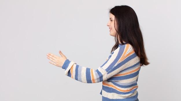 Ładna kobieta uśmiecha się, wita cię i podaje uścisk dłoni, aby zamknąć udaną transakcję, koncepcja współpracy