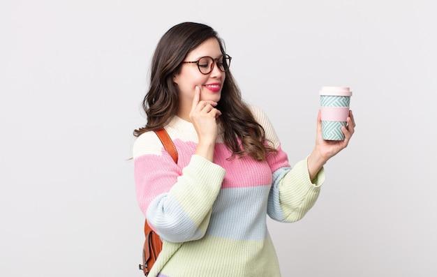 Ładna kobieta uśmiecha się ze szczęśliwym, pewnym siebie wyrazem z ręką na brodzie. koncepcja studenta