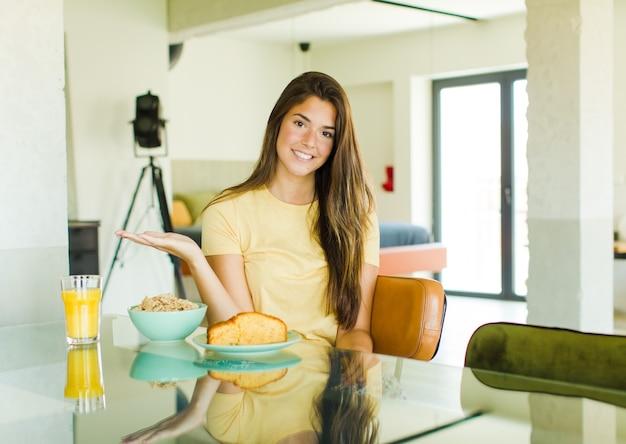 Ładna kobieta uśmiechając się radośnie, czując się szczęśliwy i przedstawiający koncepcję w przestrzeni kopii z dłoni