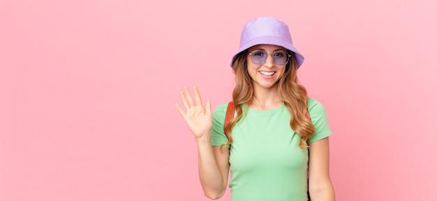 Ładna kobieta, uśmiechając się radośnie, machając ręką, witając cię i pozdrawiając. koncepcja lato