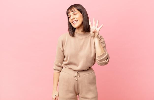 Ładna kobieta uśmiechająca się i wyglądająca przyjaźnie, pokazująca cyfrę cztery lub czwartą z ręką do przodu, odliczającą w dół