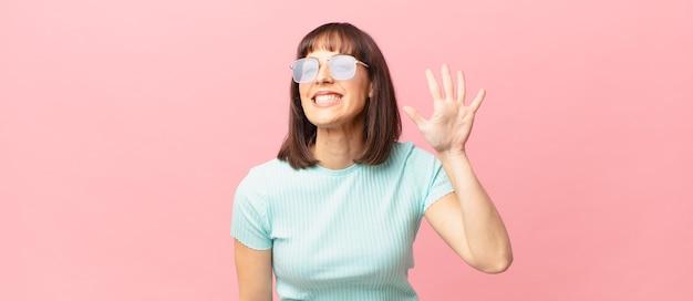 Ładna kobieta uśmiechająca się i wyglądająca przyjaźnie, pokazująca cyfrę piątą lub piątą z ręką do przodu, odliczającą w dół