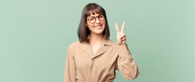 Ładna kobieta uśmiechająca się i wyglądająca przyjaźnie, pokazująca numer dwa lub drugi z ręką do przodu, odliczająca