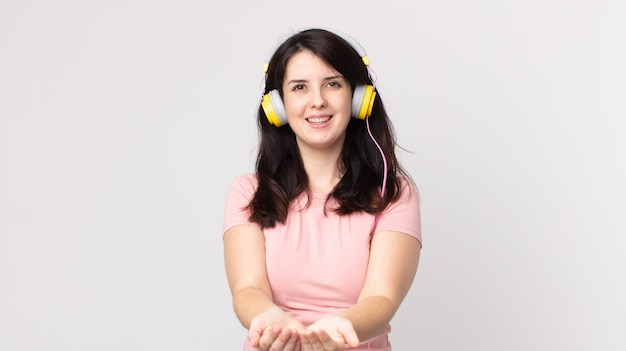 Ładna kobieta uśmiechająca się radośnie, oferująca i pokazująca koncepcję słuchania muzyki przez słuchawki