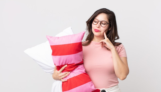 Ładna kobieta uśmiechająca się ze szczęśliwym, pewnym siebie wyrazem twarzy z ręką na brodzie, ubrana w piżamę i trzymająca poduszkę