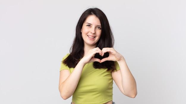 Ładna kobieta uśmiechnięta i czująca się szczęśliwa, urocza, romantyczna i zakochana, tworząca kształt serca obiema rękami