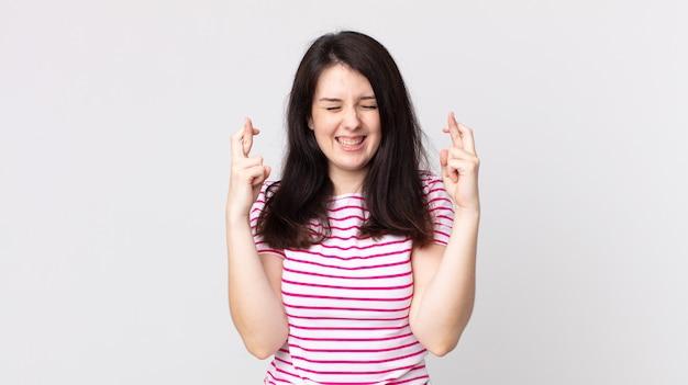 Ładna kobieta uśmiechnięta i niespokojnie krzyżująca oba palce, zmartwiona i życząca lub mająca nadzieję na szczęście