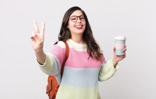 Ładna kobieta uśmiechnięta i patrząca przyjaźnie, pokazując numer dwa. koncepcja studenta