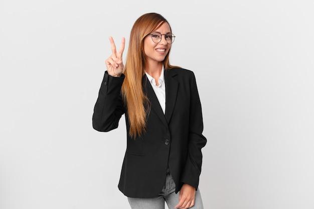 Ładna kobieta uśmiechnięta i patrząca przyjaźnie, pokazując numer dwa. pomysł na biznes