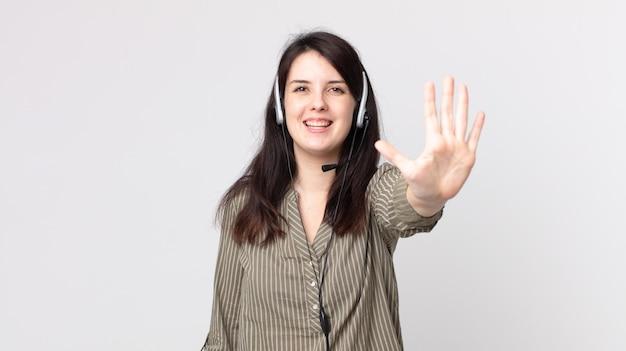 Ładna kobieta uśmiechnięta i patrząca przyjaźnie, pokazując numer pięć. asystent agenta z zestawem słuchawkowym