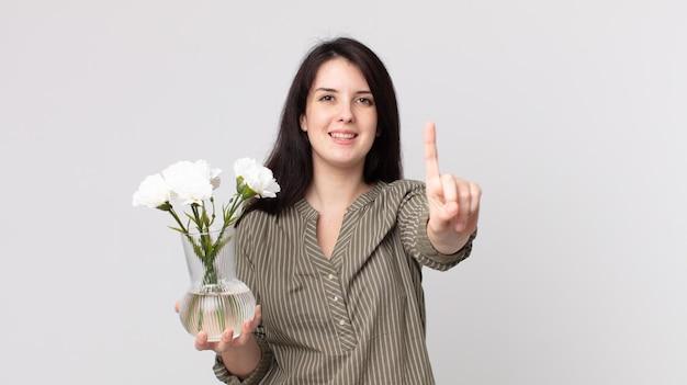 Ładna kobieta uśmiechnięta i patrząca przyjaźnie, pokazująca numer jeden i trzymająca ozdobne kwiaty. asystent agenta z zestawem słuchawkowym