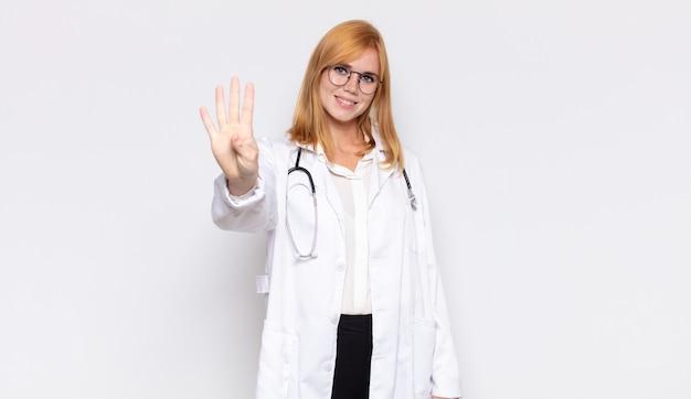Ładna kobieta uśmiechnięta i przyjaźnie wyglądająca, pokazująca cyfrę cztery lub czwarte z ręką do przodu, odliczanie