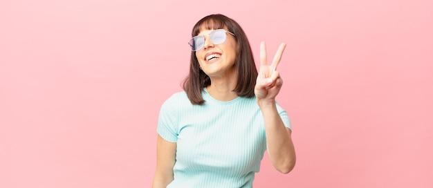 Ładna kobieta uśmiechnięta i wyglądająca na szczęśliwą, beztroską i pozytywną, gestykulującą zwycięstwo lub pokój jedną ręką