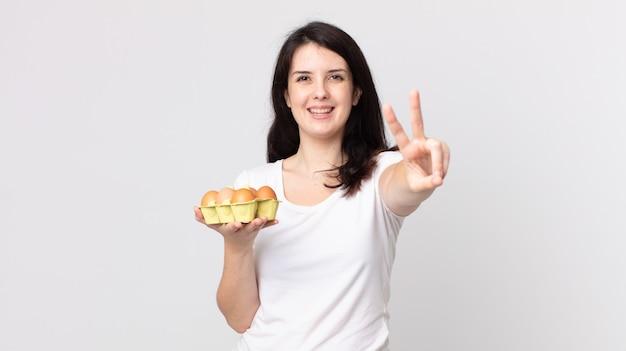 Ładna kobieta uśmiechnięta i wyglądająca na szczęśliwą, gestykulującą zwycięstwo lub pokój i trzymająca pudełko z jajkami