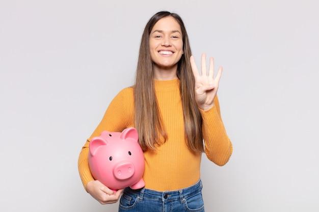 Ładna kobieta uśmiechnięta i wyglądająca przyjaźnie, pokazująca cyfrę cztery lub czwarte z ręką do przodu, odliczająca