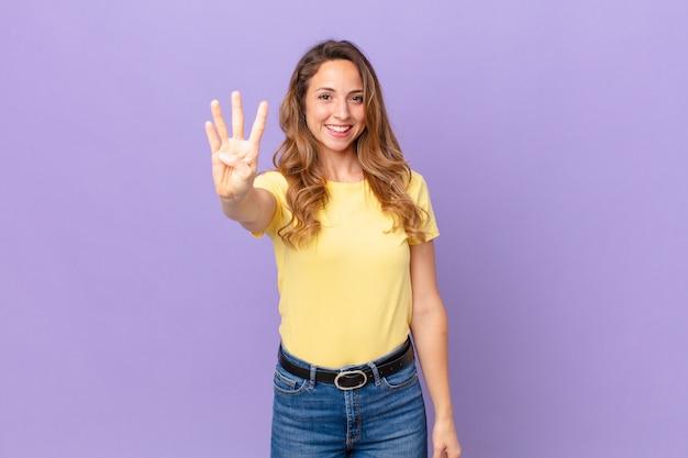 Ładna kobieta uśmiechnięta i wyglądająca przyjaźnie, pokazująca cyfrę cztery