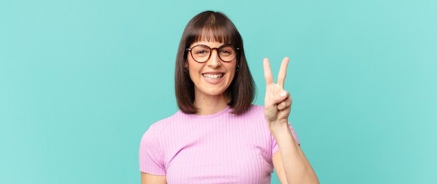 Ładna kobieta uśmiechnięta i wyglądająca przyjaźnie, pokazująca numer dwa lub drugi z ręką do przodu, odliczając w dół