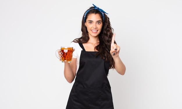 Ładna kobieta uśmiechnięta i wyglądająca przyjaźnie, pokazująca numer jeden i trzymająca kufel piwa