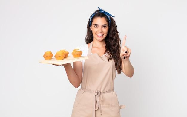Ładna kobieta uśmiechnięta i wyglądająca przyjaźnie, pokazująca numer jeden i trzymająca tacę z babeczkami