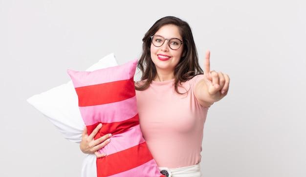 Ładna kobieta uśmiechnięta i wyglądająca przyjaźnie, pokazująca numer jeden w piżamie i trzymająca poduszkę