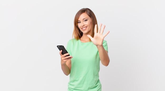 Ładna kobieta uśmiechnięta i wyglądająca przyjaźnie, pokazująca numer pięć i używająca smartfona