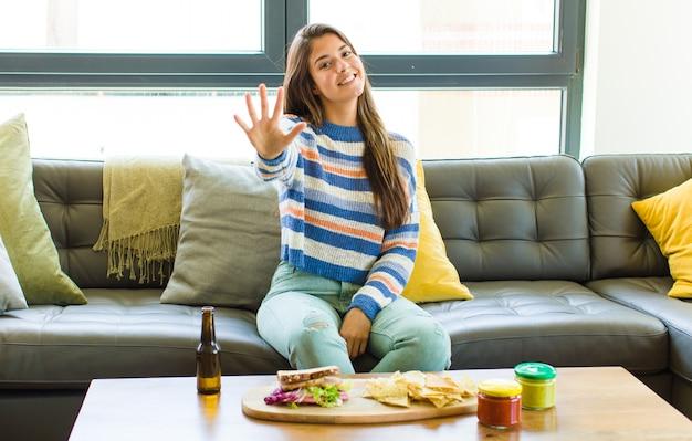 Ładna kobieta uśmiechnięta i wyglądająca przyjaźnie, pokazująca numer pięć lub piąty z ręką do przodu, odliczający