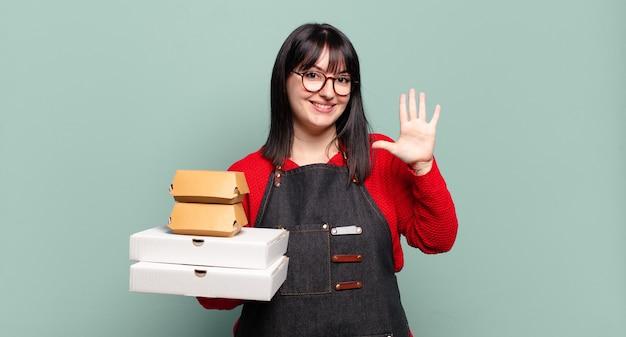 Ładna kobieta, uśmiechnięta i wyglądająca przyjaźnie, pokazująca numer pięć lub piąty z ręką do przodu, odliczający