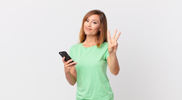Ładna kobieta uśmiechnięta i wyglądająca przyjaźnie, pokazująca numer trzy i używająca smartfona