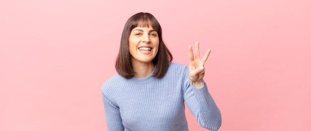 Ładna kobieta uśmiechnięta i wyglądająca przyjaźnie, pokazująca numer trzy lub trzeci z ręką do przodu, odliczając w dół