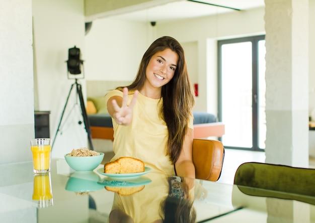 Ładna kobieta uśmiechnięta i wyglądająca przyjaźnie, pokazująca numer trzy lub trzeci z ręką do przodu, odliczający