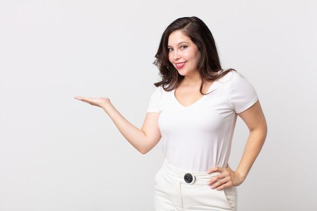 Ładna kobieta uśmiechnięta, pewna siebie, odnosząca sukcesy i szczęśliwa, pokazująca koncepcję lub pomysł na kopii przestrzeni z boku