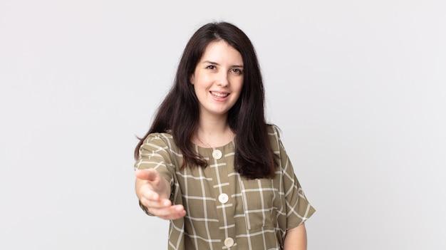 Ładna kobieta uśmiechnięta, wyglądająca na szczęśliwą, pewną siebie i przyjazną, oferująca uścisk dłoni w celu zawarcia umowy, współpracująca