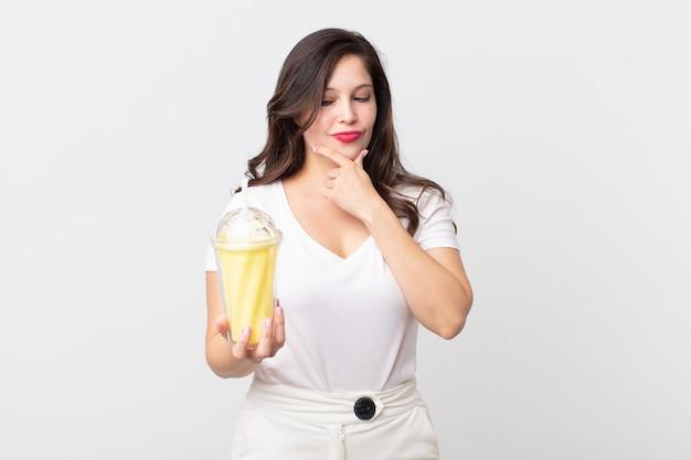 Ładna kobieta uśmiechnięta ze szczęśliwym, pewnym siebie wyrazem twarzy z ręką na brodzie i trzymająca waniliowy koktajl mleczny