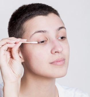 Ładna kobieta używa bawełnianego pączka do czyszczenia jej makijażu