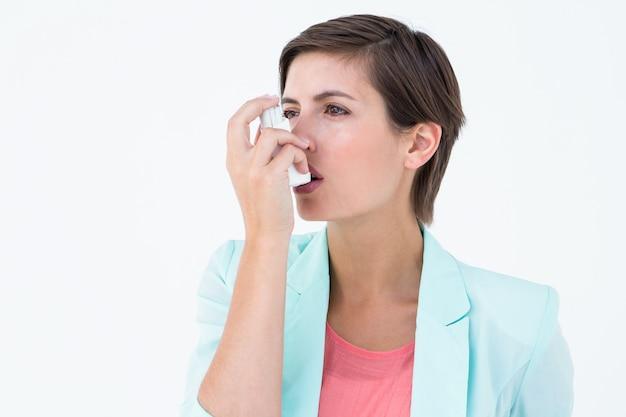 Ładna kobieta używa jej inhalator