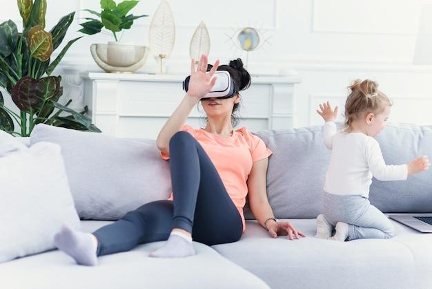 Ładna kobieta używa okularów wirtualnej rzeczywistości w domu na kanapie, podczas gdy jej córka ogląda kreskówki na laptopie