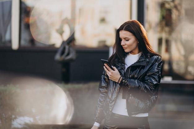 Ładna kobieta używa telefon outdoors w parku