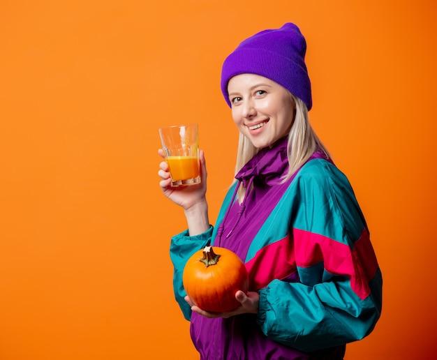 Ładna kobieta w 90s dres z sokiem z dyni na pomarańczowo