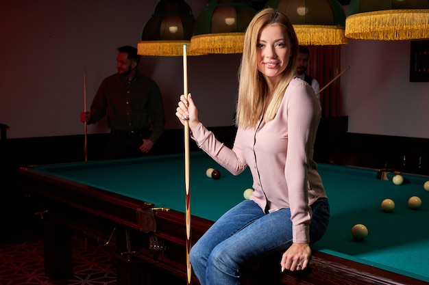 Ładna kobieta w barze obok stołu bilardowego, w tle ludzie grający w snookera. portret