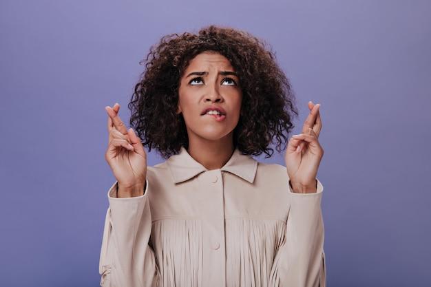 Ładna kobieta w beżowym stroju krzyżuje palce i przygryza usta