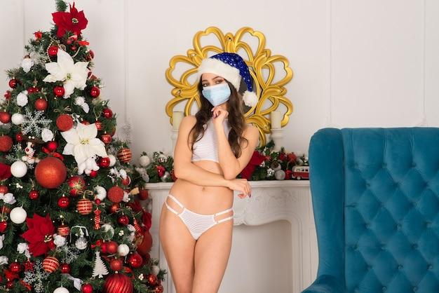 Ładna kobieta w białej bieliźnie, świątecznej czapce i masce ochronnej pozuje w pomieszczeniu w pobliżu drzewa