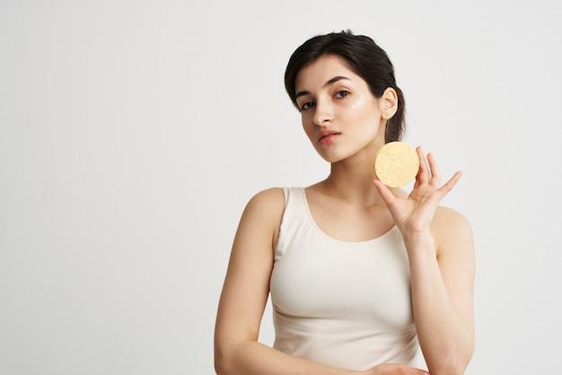 Ładna kobieta w białej koszulce gąbka w rękach usuwanie makijażu czystą skórę