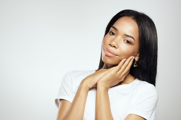 Ładna kobieta w białej koszulce pozuje modne kosmetyki