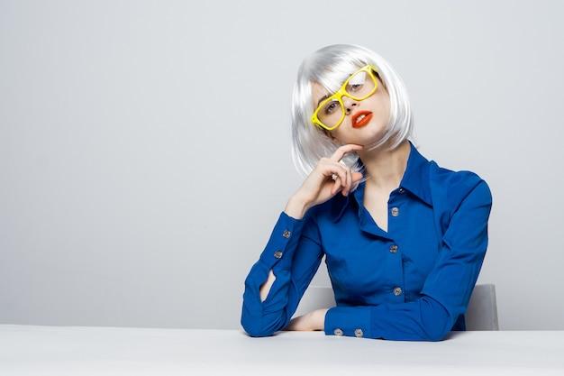 Ładna kobieta w białej peruce gestykuluje z ręki czerwone usta żółte okulary