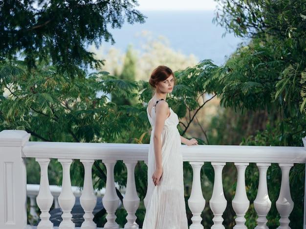 Ładna kobieta w białej sukni i luksusowym wakacyjnym parku grecja